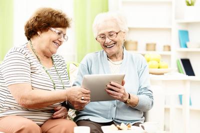 Seniorinnen mit einem Tablet benutzen die CareBW-Software.