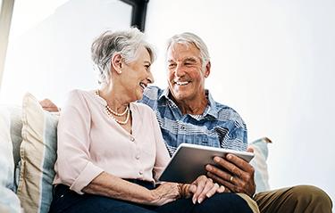Seniorenpaar nutzt CareMH Software mithilfe eines Tablets.